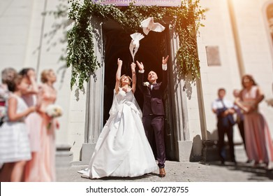 Wedding couple with releasing doves into the sky against church gate.