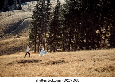 Wedding couple running on the field. Sunny day in mountains