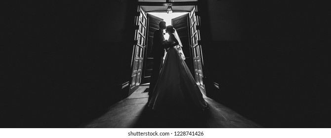 wedding couple silhouette. A husband and wife are hugged at exit of the church where the wedding took place, the silhouette of the love couple is visible. copy space for a wedding salon