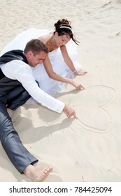wedding couple sit on sand make heart with finger on beach