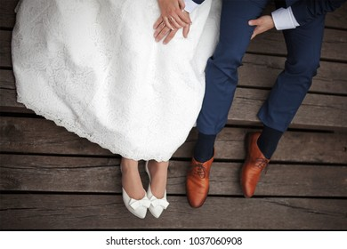 Wedding couple sitting on wooden pier.