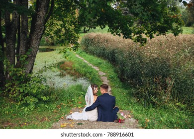 Wedding couple sitting in park in wedding day