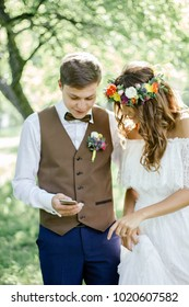 Wedding couple smiling while looking to the smartphone.