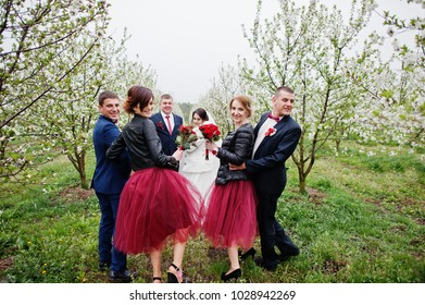 Wedding couple spending time with groomsmen and bridesmaids in he garden on a festive day.