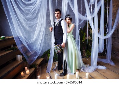 Wedding couple standing in the beautifully decorated studio in boho style. The groom holding the bridal bouquet. A lot of candles standing on the floor. Romantic wedding ceremony