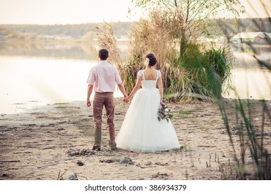 Wedding couple standing on the shore of the lake