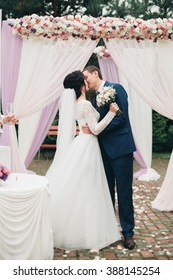 Wedding couple standing under an arch of fresh flowers
