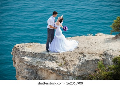 wedding couple stands on a cliff above blue sea