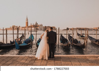 A wedding couple stands on the pier in Venice. Boats float on the water. Early morning sunrise warm summer weather. Bride in white dress groom in business black classic suit in Italy.