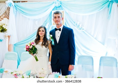 Wedding couple stay near table at restaurant