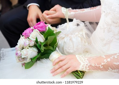 Wedding couple with a stylish bouquet of roses holding each other's hands