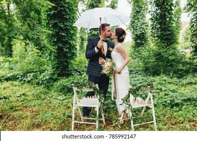 Wedding couple with umbrella kissing near decorative folding chairs