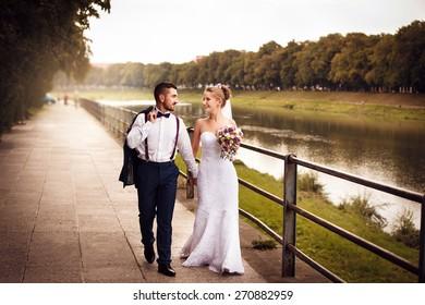 Wedding couple walk hand in hand along the promenade