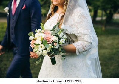 Wedding couple walking in the green park. Curvy bride in white lace dress and groom are holding hands. Overweight happy people. Love story outdoors. Beautiful bouquet.