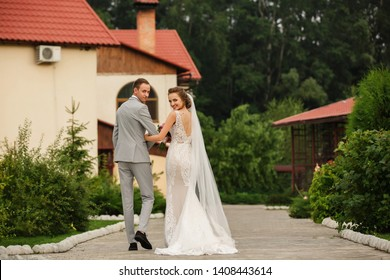 Wedding couple walking near wedding place ceremony. Rear view of the bride and groom. Stylish newlywed couple. Marriage concept