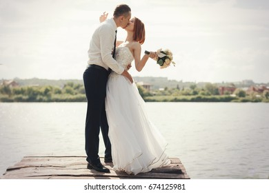 Wedding couple walking on bridge near lake on sunset at wedding day. Bride and groom in love. Woman in white dress main white shirt and tie