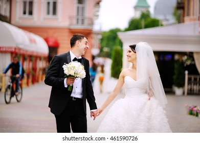 Wedding couple walking street, groom and bride holding hands happy together