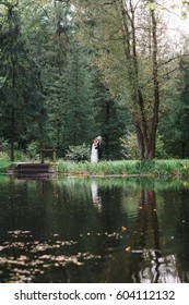 Wedding couple walks along lake's shore in the park