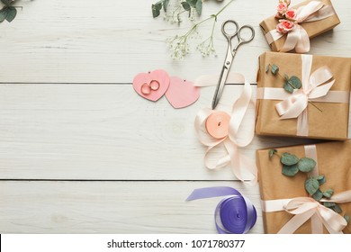 Wedding craft gift boxes on white wooden background. Top view on ribbons, flowers and scissors, copy space. Memmorable date organization concept