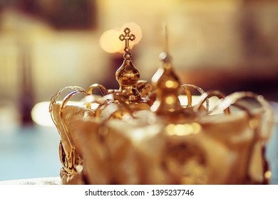 Wedding crown in church ready for marriage ceremony. close up Divine Liturgy. golden wedding crowns on church table