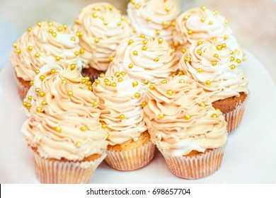 Wedding cupcakes with butter-cream frosting in gold cupcake liners.