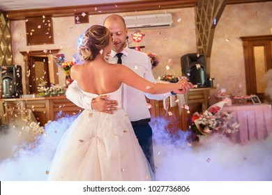 Wedding dance of bride and groom with special effects- colorful smoke. newlyweds couple dancing at wedding day. Marriage and wedding party concept