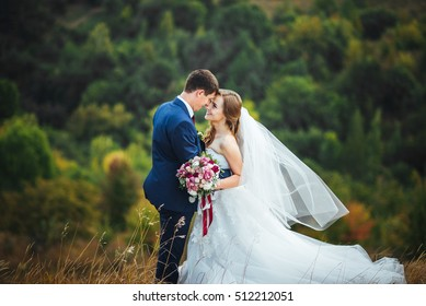 Wedding. Wedding day. Beautiful bride and elegant groom walking after wedding ceremony. Luxury bridal dress and bouquet of flowers. Bride and groom at wedding day