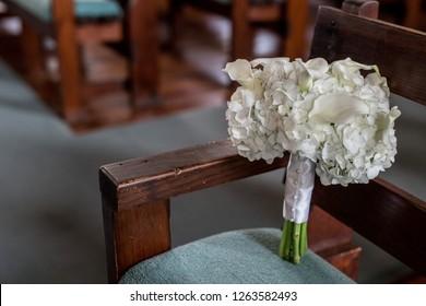 Wedding day bouquet sitting on antique church pew