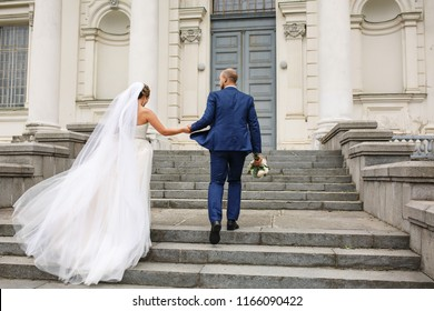 Wedding day. Bride and groom holding hands and walking near church after wedding ceremony. Newlyweds couple in love. Marriage concept