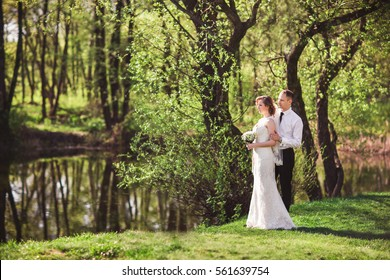 Wedding day, bride and groom near river.