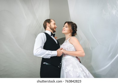 Wedding day. The bride and groom near a bright window. Under the translucent cloth. Hold each other's hand.