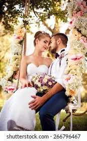 Wedding day. Bride and groom sit on beautiful decorated swing