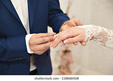Wedding day. Ceremony. Wedding hands with rings. The groom puts the bride on the finger of the engagement ring. Close up