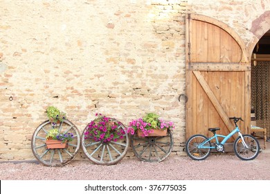 WEDDING DAY AT CHATEAU DE SALORNAY, FRANCE-July 17, 2014 on the wedding day, the place decorated on  nice wall with flowers on wheels and blue bicycle against the big door.