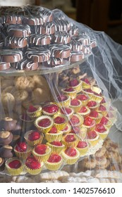 Wedding day cookie table covered by veil with buckeyes and cheesecake bites among other baked goods