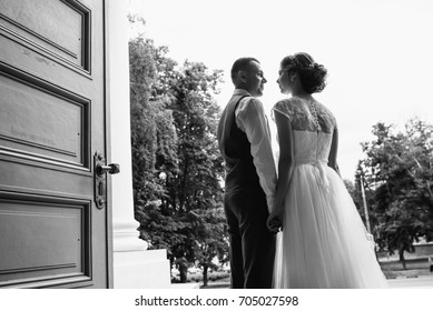 Wedding. Wedding day. Wedding couple. Beautiful couple, bride and groom look at each other and smiling against a white castle.