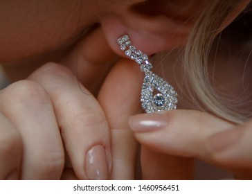 Wedding day. Wedding earrings on a female hand, she takes the earrings, the bride fees, morning bride, white dress, wear earrings. Earrings close-up in the hands of the bride. jewelry accessories