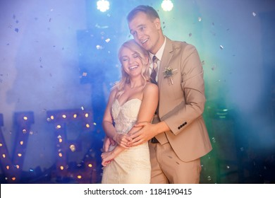 Wedding day. First wedding dance of stunning bride and attractive groom, cheerfully smiling, bubbles. Love. Marriage. Indoors.