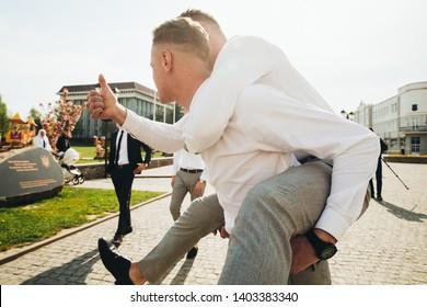 Wedding. Wedding day. Groom with groomsmen walking after wedding ceremony. Handshakes. Groom with friends at wedding day