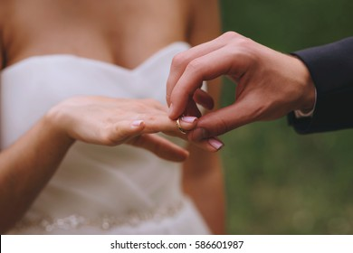 Wedding day. The groom places the ring on the bride's hand. Photo closeup