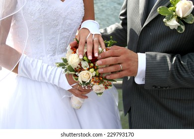 Wedding day hands and rings on flowers