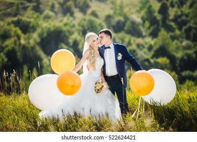 Wedding. Wedding day. Happy bride with bouquet of flowers and elegant groom with helium balloons. Cute couple kissing and standing on background of nature after wedding ceremony. Wedding concept.