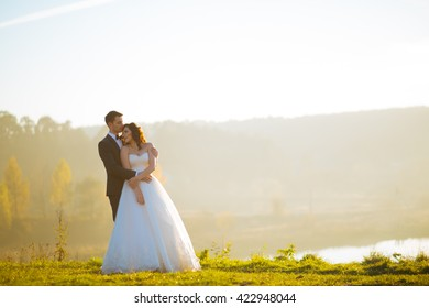 Wedding day. Marriage. Wedding walk outdoors. Newlyweds with bouquet of flowers. Bride and groom portrait. Love, feelings, tenderness. Marriage bond