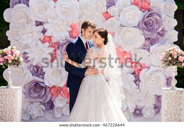 Wedding. Wedding day. Paper flowers in wedding decor. Bride and groom on wedding ceremony with luxury wedding decoration. Wedding decoration, ceremony. Beautiful bride and elegant groom on ceremony.