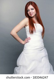 Wedding day. Portrait of happy beautiful blue eyed red haired bride long white dress in full length studio shot on gray background