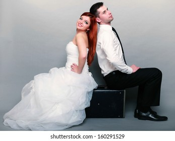 Wedding day. Portrait of happy married couple red haired bride and groom in full length sitting on old suitcase back on back studio shot on gray background. Honeymoon and travel