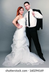 Wedding day. Portrait of happy married couple red haired bride and groom in full length studio shot on gray background