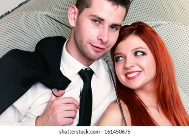 Wedding day. Portrait of happy married couple red haired blue eyed bride and groom with umbrella studio shot on gray background