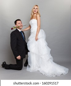 Wedding day. Portrait of romantic married couple blonde bride and enamored groom giving a rose to girl. Full length studio shot gray background