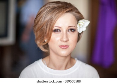 Wedding day. Portrait of a young woman, a bride on the wedding day. Preparation, makeup, do her hair, the hair are crazy, do bouffant comb. The image of orchid flowers